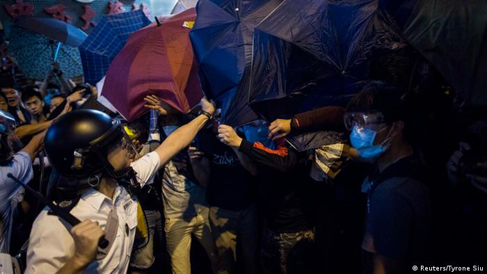 A riot policeman takes an umbrella from a pro democracy protester during a scuffle on a blocked road at Mongkok shopping district in Hong Kong October 17, 2014. REUTERS/Tyrone Siu