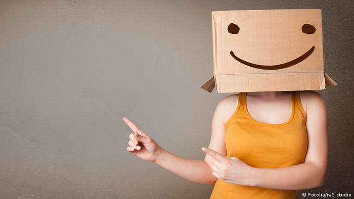 Young lady gesturing with a cardboard box on her head with smile (Photo: ra2 studio)
