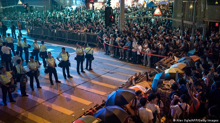 Police officers stand guard at an intersection that had been part of a pro-democracy occupation but was taken back by force as protesters and onlookers gather in the Mongkok district of Hong Kong on October 18, 2014. Alex Ogle/AFP/Getty Images