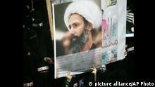 FILE - In this Sunday, Sept. 30, 2012 file photo, a Saudi anti-government protester carries a poster with the image of jailed Shiite cleric Sheik Nimr al-Nimr during the funeral of three Shiite Muslims allegedly killed by Saudi security forces in the eastern town of al-Awamiya, Saudi Arabia. Mohammed al-Nimr, the brother of Nimr al-Nimr said Wednesday, Oct. 15, 2014, on Twitter that his brother has been sentenced to death by a court in Saudi Arabia. Shiite activist Jaafar al-Shayeb in eastern Saudi Arabia says the verdict appears to have been handed down for criminal offenses over the incitement of Shiite protests in Saudi Arabia and neighboring Bahrain. The headbands read, martyrdom is honor and dignity. (AP Photo, File)