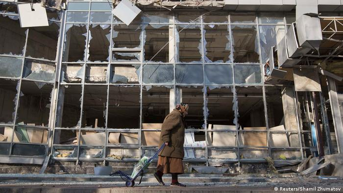 A woman pulls her shopping trolley as she walks past a building that was damaged by shelling in Donetsk, eastern Ukraine, October 15, 2014. REUTERS/Shamil Zhumatov