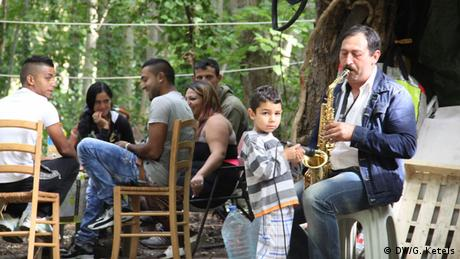 A young boy holds a microphone as a man plays the saxophone – the music is being played as part of a birthday party for one of the women at a Roma slum in Paris, France. The party goers sit laughing in the background. The community live in terrible conditions in the middle of a group of trees in the French capital with constant fear of being evicted from the site.