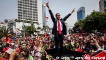 Bildunterschrift:JAKARTA, INDONESIA - OCTOBER 20: I ndonesian President Joko Widodo waves to the crowd while on his journey to Presidential Palace by carriage during the ceremonial parade on October 20, 2014 in Jakarta, Indonesia. Joko Widodo was sworn in October 20, as the president of Indonesia with an inauguration ceremony held in Jakarta. Widodo was the eventual winner of a tightly fought and sometimes controversial election race against opposition candidate Prabowo Subianto. A number of key world leaders were in attendance including Australia's prime minister Tony Abbott. (Photo by Ulet Ifansasti/Getty Images)