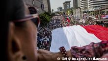 Bildunterschrift:JAKARTA, INDONESIA - OCTOBER 20: People watch as an Indonesian flag is carried on the street while Indonesian President Joko Widodo and Vice President Jusuf Kalla journey to Presidential Palace by carriage during the ceremonial parade on October 20, 2014 in Jakarta, Indonesia. Joko Widodo was sworn in October 20, as the president of Indonesia with an inauguration ceremony held in Jakarta. Widodo was the eventual winner of a tightly fought and sometimes controversial election race against opposition candidate Prabowo Subianto. A number of key world leaders were in attendance including Australia's prime minister Tony Abbott. (Photo by Ulet Ifansasti/Getty Images)