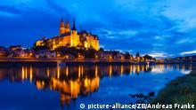 Ein beleuchtetes Schloss in der Dämmerung, das sich, ebenso wie die davor liegende Ufernstraßenbeleuchtung, im Fluss davor spiegeln