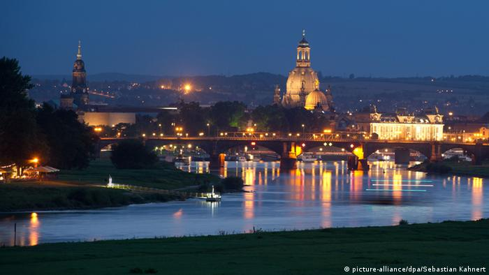 A view of Dresden at night fall acoss the river Elbe, reflecting the lights of the city and the illuminated dome of the Frauenkirche church.
