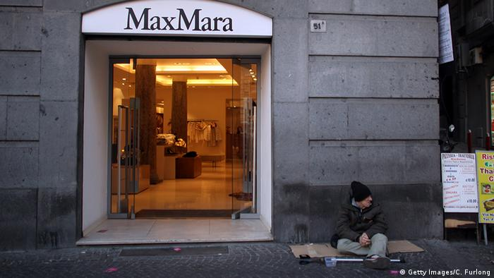 A beggar with a crutch in front of a Max Mara store in Naples
