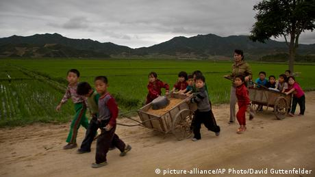 Children repair a road in the rural countryside of North Korea