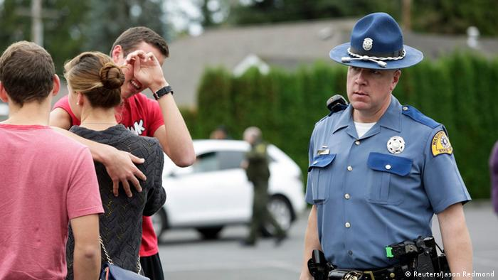 A state trooper walks by a grieving student as students and family members reunite at Shoultes Gospel Hall, following a school shooting at Marysville-Pilchuck High School, in Marysville, Washington October 24, 2014. (Photo: REUTERS/Jason Redmond)