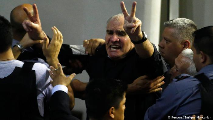 Hector Acuna (C), a former army officer gestures as he is taken away from a courtroom after hearing the verdict in the final stage of their trial for their role in the kidnapping, murder and torture of people during the Argentina's last dictatorship in the notorious clandestine detention centre known as La Cacha, in La Plata, Buenos Aires province October 24, 2104. REUTERS/Enrique Marcarian