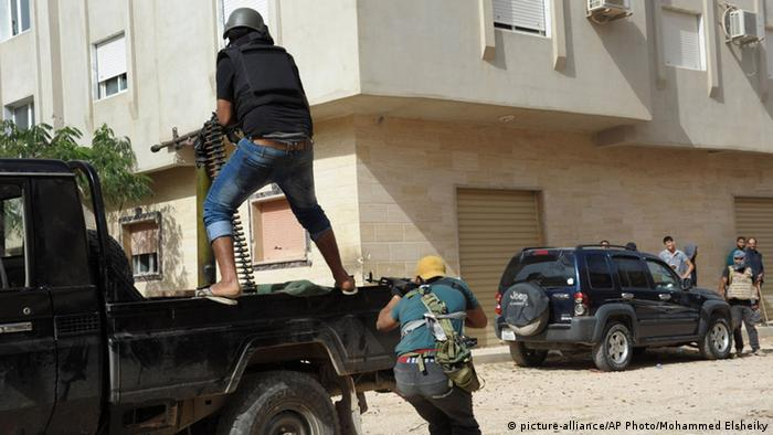 Libyan people hold weapons to defend their local area from Islamic militias in Benghazi