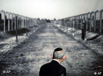 Israel Singer, Secretary General of the World Jewish Congress looks to a photo showing a way in the Nazi concentration camp Auschwitz