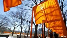 ** USA NEW YORK GATES ** People walk under a section of The Gates art installation created by Christo and Jeanne-Claude in New York's Central Park, Wednesday, Feb. 23, 2005. The Gates features 7,500 frames with their hanging orange-tinted fabric, creating what the artists billed as ``a visual golden river'' along 23 miles of footpaths in the park. (AP Photo/Mary Altaffer)
