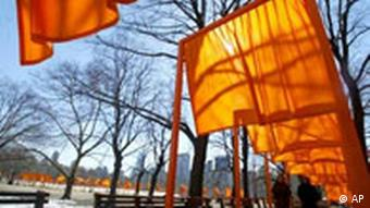 Visitors stroll under large orange gates designed by Christo and Jeanne-Claude in New York