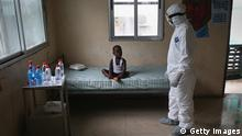 MONROVIA, LIBERIA - OCTOBER 03: A Liberian health worker dressed in an anti-contamination suit speaks with a boy at a center for suspected Ebola patients, formerly the maternity ward at Redemption Hospital on October 3, 2014 in Monrovia, Liberia. People at the center are tested for Ebola and if the results are positive, are sent to an Ebola treatment unit (ETU). The epidemic has killed more than 3,300 people in West Africa according to the U.S. Centers for Disease Control (CDC). (Photo by John Moore/Getty Images)