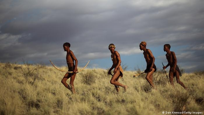 San hunter-gatherers carrying traditional weapons, including a bow and arrows