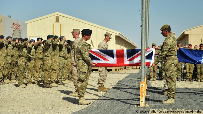 British soldiers and US Marine Corps (USMC) soldiers attend the ceremony of the British, US and NATO flags being lowered at the Camp Bastion-Leatherneck camp complex for the last time in Afghanistan
