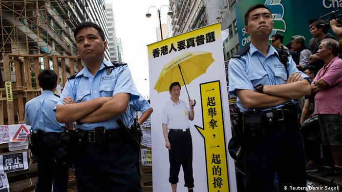 Police stand beside a cutout made by pro-democracy protesters featuring a manipulated photo of Chinese President Xi Jinping holding an yellow umbrella, at Mongkok shopping district in Hong Kong October 26, 2014. The banner reads, Hong Kong people want universal suffrage. Together we raise umbrellas, together we persevere. REUTERS/Tyrone Siu