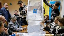 Members of a local electoral commission empty a ballot box at a polling station after voting day in Kiev, October 26, 2014. Ukrainian President Petro Poroshenko hailed a sweeping victory for pro-Europe parties in an election on Sunday, saying the vote showed people backed his plan to end a separatist conflict, his pro-Western course and democratic reforms. REUTERS/Gleb Garanich (UKRAINE - Tags: POLITICS ELECTIONS)