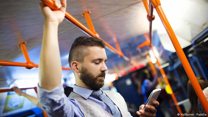 Молодой человек со смартфоном едет в автобусе