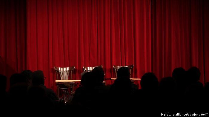 Ein roter Vorhang auf einer Theaterbühne, davor die Schatten von Zuschauern