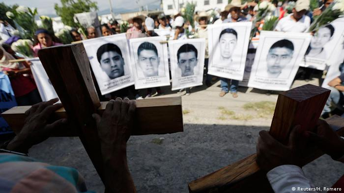 Protest signs show the faces of the missing students in Mexico