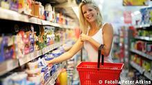 Deutschland Frau mit rotem Einkaufskorb im Supermarkt