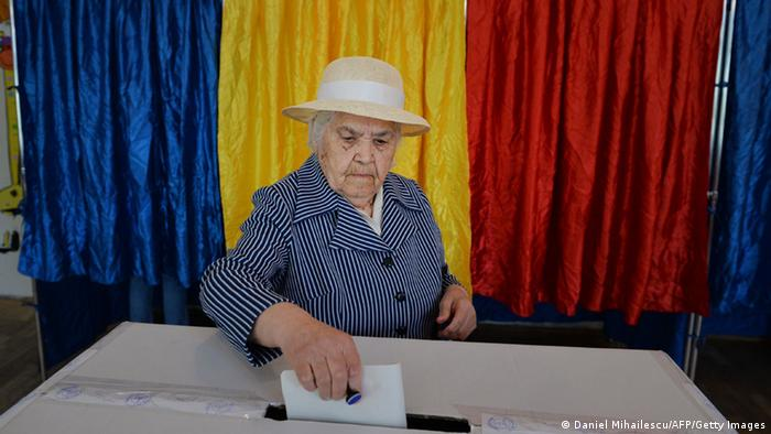 A Romanian woman casts her ballot for the European Parliament elections near booths featuring the national colors of Romania at a polling station in Bucharest on May 25, 2014. DANIEL MIHAILESCU/AFP/Getty Images