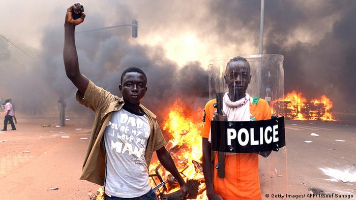 Two demonstrators, one holding a police shield, pose in front of the burning parliament (Getty Images/ AFP/ Issouf Sanogo)