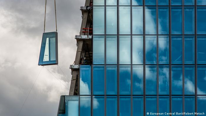 A crane places a window on the ECB office tower