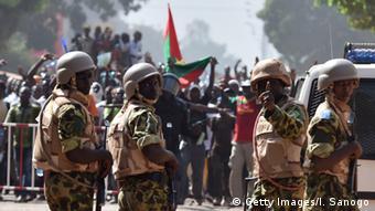 Sicherheitskräfte stehen mit Maschinenegewehren vor den aufgebrachten Demonastranten. Im Hintergrund reicht die Rauchsäule aus dem Präsidentenpalast bis in den Himmel. (Foto: Getty Images/I. Sanogo)