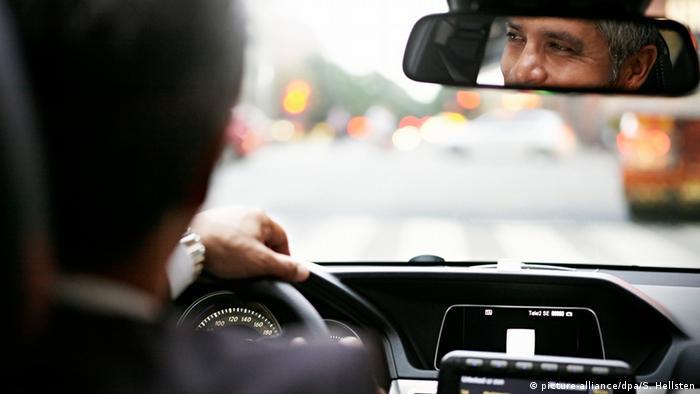 Un hombre sentado en un coche mirando por el espejo retrovisor.