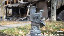 The remains of a projectile is seen in front of shops damaged by recent shellings in Donetsk, eastern Ukraine, October 21, 2014. REUTERS/Shamil Zhumatov (UKRAINE - Tags: POLITICS CIVIL UNREST)