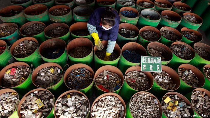 A woman sorts through barrels containing used batteries and other e-wastes
