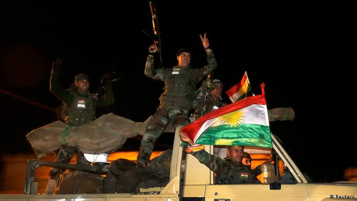 Kurdish peshmerga fighters wave Kurdish flags atop an army vehicle as they move towards the Syrian town of Kobani from the border town of Suruc, Sanliurfa province, October 31, 2014. REUTERS/Yannis Behrakis