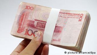 A man shows a bundle of RMB (renminbi) yuan banknotes in Ji'nan city, east China's Shandong province, 20 September 2014