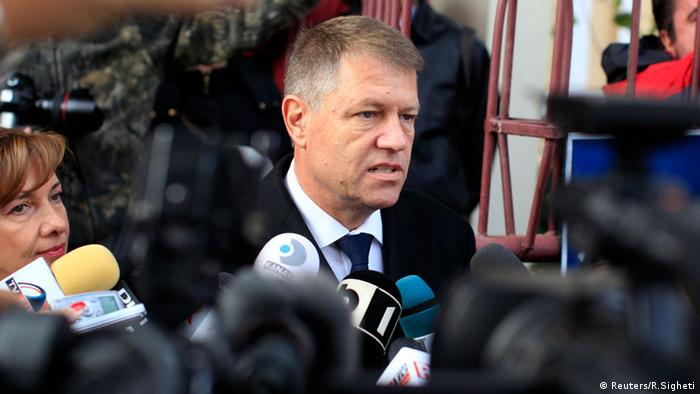 Klaus Iohannis stands in front of reporters' microphones