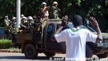 A man gestures as Burkinese troops arrive to the national television headquarters after shots were fired around the premises in Ouagadougou on November 2, 2014. The army in Burkina Faso, which seized power after the ouster of the country's long-standing president Blaise Compaore, took over national television headquarters, AFP journalists at the scene said. AFP PHOTO / ISSOUF SANOGO (Photo credit should read ISSOUF SANOGO/AFP/Getty Images)