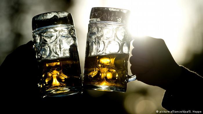Zwei Menschen stoßen mit großen Biergläsern an