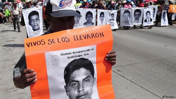 Ein Demostrant in Mexiko hält ein Foto von einem der offenbar ermordeten Studenten (Foto: Reuters)