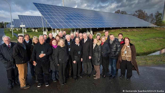 A group of people in front of a large solar panel. (Photo: Gemeinde Saerbeck)