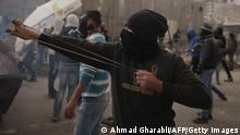 A Palestinian protester fires a slingshot during clashes with Israeli security forces in the Palestinian refugee camp of Shuafat in east Jerusalem, on November 5, 2014, after a Palestinian rammed his vehicle into a crowd of pedestrians in Jerusalem. A Palestinian slammed his car into pedestrians in Jerusalem, killing a border policeman and wounding nine other people in the second such attack in recent weeks. AFP PHOTO/ AHMAD GHARABLI (Photo credit should read AHMAD GHARABLI/AFP/Getty Images)
