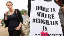 A woman looks at a cloth tote bag with Home is where Berghain is written on it (Adam Berry/Getty Images)