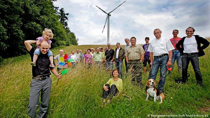 Bürger der Energiegenossenschaft Starkenburg stehen vor einer Windanlage und freuen sich, dass sie selbst etwas für den Klimaschutz tun.
