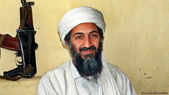 Porträt von Osama bin Laden neben einer Waffe