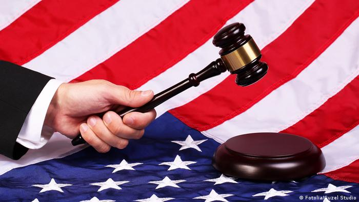 Человек держит молоток судьи на фоне флага США