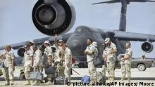 U.S. soldiers wait to board a C-5 transport plane bound for Dover Air Force Base, Delaware, at Mogadishu Airport, March 24, 1994, as the American military presence in Somalia draws to a close. All remaining American troops will leave Somalia on Friday. (AP Photo/John Moore)