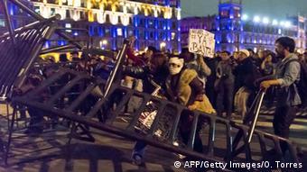 Umgekipptes Drängelgitter und vermummte Demonstranten bei Protesten wegen der mutmaßlichen Ermordung der vermissten Studenten in Mexiko-Stadt am 8.11.2014 (Foto: AFP/Gety Images/O. Torres))
