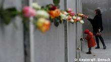 A mother and young daughter place roses at the Berlin Wall memorial in Bernauer Strasse, during a ceremony marking the 25th anniversary of the fall of the Berlin Wall, in Berlin November 9, 2014. REUTERS/Fabrizio Bensch (GERMANY - Tags: POLITICS ANNIVERSARY SOCIETY)