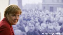 German Chancellor Angela Merkel stands in front of a photograph showing Bernauer Strasse in November 1989 as she visits an exhibition during a ceremony marking the 25th anniversary of the fall of the Berlin Wall at a memorial in Bernauer Strasse in Berlin, November 9, 2014. REUTERS/Fabrizio Bensch (GERMANY - Tags: POLITICS ANNIVERSARY SOCIETY)